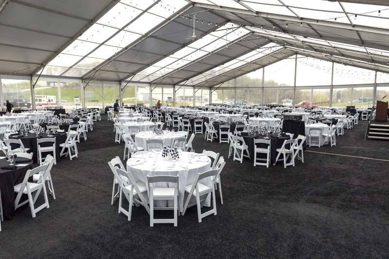 Several black and white tables and chairs in an indoor enclosure